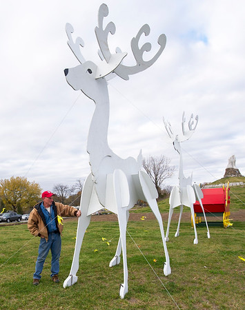 Webb City Parks crew leader Joe Raines secures the cables on a 19-foot reindeer on Friday at Kng Jack Park. The display will be one of about nine for the tour on the Polar Express, which begins running Dec. 3.<br /> Globe | Laurie Sisk