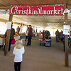 Visitors check out the holiday-themed items booth on Saturday at the Christkindlmarket inside the Webb City Farmer's Market.<br /> Globe | Laurie Sisk