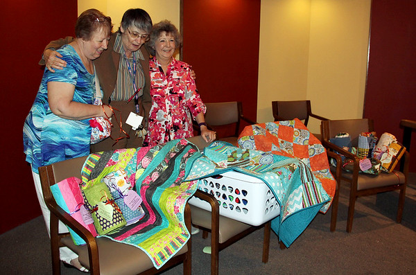 Freeman Contributed Photo<br /> (left to right) Mary Drain, Medella Quilters; Christine Iannucilli, Freeman Chaplain; and Dana Parker, Medella Quilters, look over quilts donated by the Medella Quilters of Joplin to Freeman Pastoral Care at Freeman Hospital West Chapel on Thursday. The 14 donated quilts will be distributed to patients at Freeman Health Syestems by chaplins for comfort in their recovery or illness.