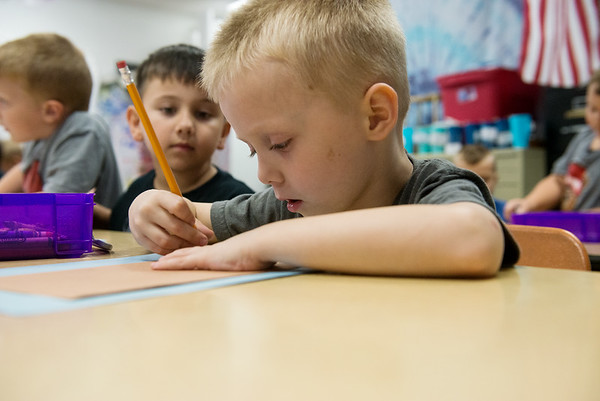 Globe/Roger Nomer<br /> Erick Lira-Munoz watches as Bently Miksell traces his hand during an art exercise in kindergarten at Jasper Elementary on Thursday.