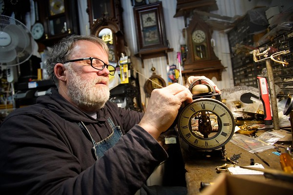 BEN GARVER — THE BERKSHIRE EAGLE<br /> Aldo Battaini dissects a copy of a lantern clock for cleaning at the West Side Clock Shop in Pittsfield. One of the last shops of its kind, Aldo does repairs in the corner of the showroom.