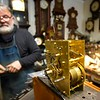 BEN GARVER — THE BERKSHIRE EAGLE<br /> Aldo Battaini walks past a 19th century brass clockworks he recently cleaned at the West Side Clock Shop in Pittsfield. One of the last shops of its kind, Aldo does repairs in the corner of the showroom.