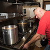 Lynn firefighter Bobby Lehman fires up a burner to warm up gravy for the annual Thanksgiving luncheon for the children of Gregg House.