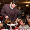 State Rep. Brendan Crighton pours gravy for Gianna LoPresti, 5, during the annual Thanksgiving luncheon hosted by Lynn firefighters for the children of Gregg House on Wednesday.