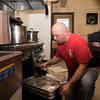 Lynn firefighter Bobby Lehman pulls food for the Thanksgiving luncheon for the children of Gregg House out of the oven.