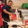 Lynn firefighter Mario Lopez helps make the mashed potatoes for the annual Thanksgiving luncheon for the children of Gregg House on Wednesday.