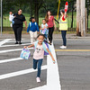Kalea Johnson, 6, can't control her excitement as she sprints ahead of, from left, Janaya Pierre-Louis, Alexis Pierre-Louis, Amira Rocker, 7, Amyra Johnson, 6, Amanda Passia, and crossing guard Catherine Pahlm, on her way to start her first day of school at the Julia F. Callahan School on Wednesday.
