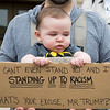 "Five-month-old Thomas Smith-Vaughan of Lynn holds up a sign that reads ""I can't even stand yet and I'm standing up to racism. What's you excuse, Mr. Trump?"" during the Rally and March Against Racism in Lynn on Saturday."