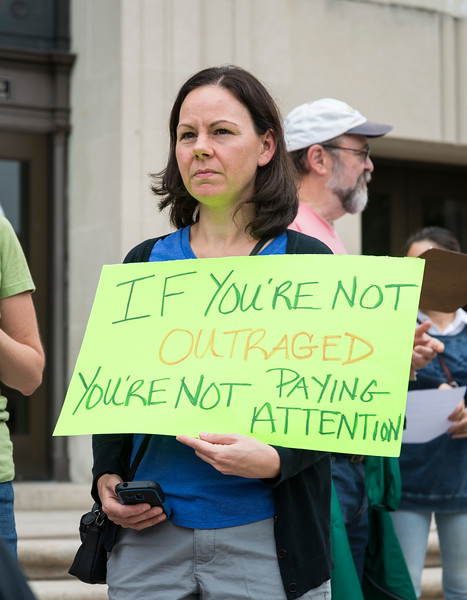 """Karyn King Fargo of Peabody holds a sign that reads """"If your're no outraged, you're not paying attention"""" during the Rally and March Against Racism in Lynn on Saturday. Fargo's sign was inspired by the final Facebook post of Heather Heyer, who was killed while protesting in Charlottesville."""