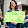 "Karyn King Fargo of Peabody holds a sign that reads ""If your're no outraged, you're not paying attention"" during the Rally and March Against Racism in Lynn on Saturday. Fargo's sign was inspired by the final Facebook post of Heather Heyer, who was killed while protesting in Charlottesville."