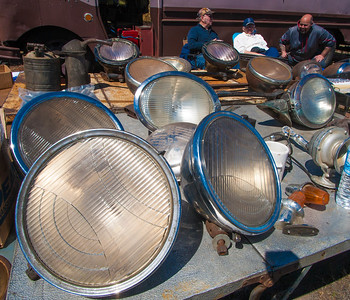 """Three bright guys,"" Don Axelrod (left), owner of 'Headlight Headquarters' in Lynn along with Stan and Adam Laub, all of Lynn sit behind a table full of old headlights at the 45th Annual Early Ford V8 Club of N.E. Spring Tune Up at the Fitchburg Airport."