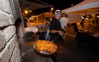 Ken Robichaud of K&L's Brick Oven Bistro of Templeton takes out another pizza from the mobile brick oven as the Leominster Full Moon Food Truck Festival winds down.