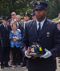 Fitchburg FF Robert Dacosta bears the helmet of fellow FF Jimmy Roy at the conclusion of his funeral with full department honors. Behind is widow Denise Roy flanked by her sons Patrick James (PJ) and Sean both also Fitchburg Firefighters. Jimmy died of occupational cancer 5 days shy of his 40th year on the job.