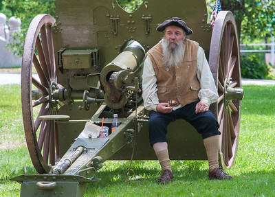 "Nathan Stiles, Jr of Ashburnham, a member of the Ashburnham Light Infantry ""1791"" sits in period dress eating a modern era donut while perched on a WW I cannon during the opening of time capsules at Ashburnham Town Hall."