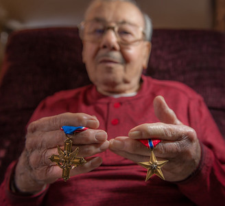 LEOMINSTER - Santo J. DiSalvo a Staff Sgt in the U.S. Army during WWII holds his Distinguished Service Cross and Bronze Star in his Leominster home. Thursday, December 28, 2017 {Photo/Jim Marabello]