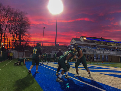 Fitchburg State University players warm up under a brilliant sunset prior to the of the ECAC Div III Scotty Whitelaw Bowl At Central Connecticut State in New Britain, Ct.
