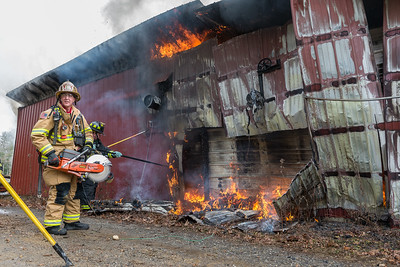 RUTLAND - A Holden firefighter works on opening a metal wall at a structure at Putnam Services, 549 East County Rd, Rutland. The fire was in a building filled with firewood. Friday, December 8, 2017. [Photo/ Jim Marabello]