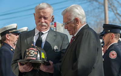 Helmet bearer Ret FF Richard Hawthorne & retired FF Billy Burke look at the helmet of Jack Mulcahy