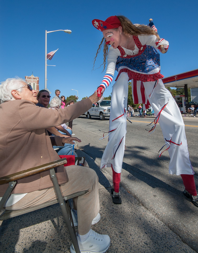 Molly the Stiltwalker of Amesbury greets a parade goer in Leominster during the city's 100th Anniversary parade.