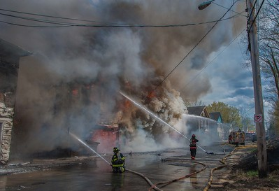 Gardner firefighters begin to get water on a fully involved vacant factory on Sherman St at the begnnings of a 6 Alm fire. Winner of an Honorable Mention in the 2016 IAFF Media Awards.