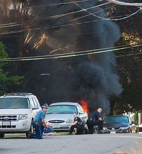 Gardner police officers and a State Trooper take cover with weapons drawn as 2 cars burn in the driveway at 99 Graham St. There were reports of shots fired and a barricaded subject with hostage. A subject from the house is also being sheltered behind another car. SENTINEL& ENTERPRISE/ Jim Marabello