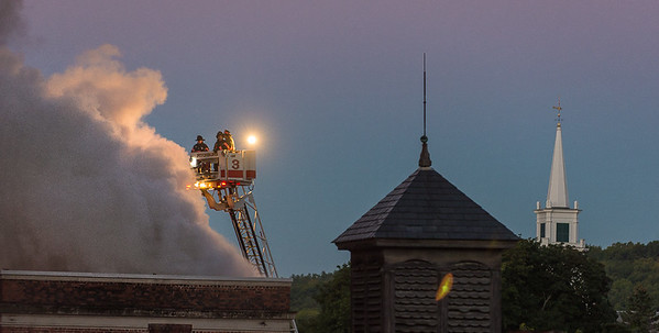 Smoke billows from the roof of the former BF Brown School as Fitchburg Firefighters man one of the TowerLadders at dawn, with the steeple of First United Parish in the background.