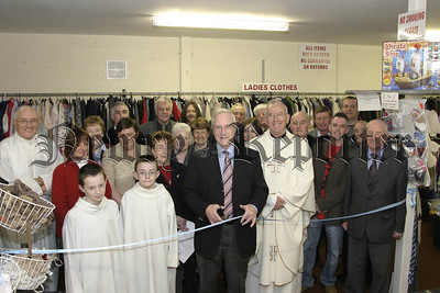 Area President of St Vincent De Paul cuts the Ribbon to open the Newly Renivated Premises of the Sacred Heart Conference as members look on, with Fr Stanley and Fr Naughton of Middle Killeavey and Alter boys Colm & Fergal Murphy. 05W16N57.