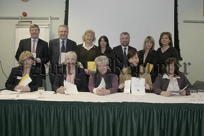 Top Table at the Newry & District Alzheimers Society AGM in Bally-Bot house, Front l-r, Francis Mc Mahon (outreach worker),Lilian Mc Kevitt(asst treasurer),Maura Mc Quaid (treasurer), Catriona Ruanne (MLA), Pauline Murphy (adminastrator). back l-r, Kieran Hanna (chairperson), Danny Kennedy (MLA), Marie Hanna (comm),Marylin Sweeney (comm), Davy Hyland (MLA), Sharon Murphy (secretary) & Susan Mackin (comm).  05W8N55.