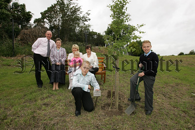Former pupil Jonathan Adams and current pupils at Mullaglass P.S. William Adams plant a tree in memmory of  their Grandfather and former pupils George Hawthorne, Also pictured are Principal Mrs H. Jenkinson, Mrs R. Hawthorne, Mr J. Adams, Mrs G. Adams and little Katie Adams. 07W27N7