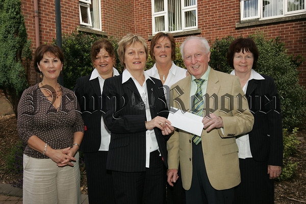 Gervase McCartan Chairman Newry Cancer Research recieves a cheque from the Newry and Mourne Council team which participated inthe Annual Cancer Research All day walk held in Frank Curran Park on the 16th June and managed to raise £1000, The Team which took part were, Bridget Doran, Brenda Byrne, Briege McNaklly, Celine McKeown, Ann Smith, Jaqueline Turley, Veronica McGeeney, Marie Delahunt and Hilary Halliday. 07W30N8