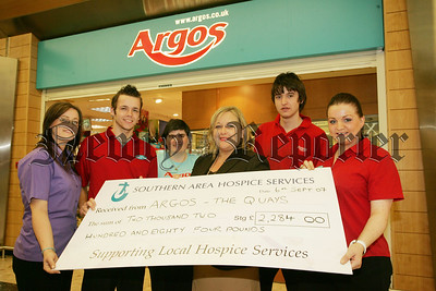 Maurice Fegan presents Fiona Stevens from the Southern Area Hospice with a  cheque for £2284 the proceeds of a funday held in the Quays on the 26th May. Also pictured are Staff at Argos, Danielle Lynch, Kathy Locke, Diane Magowan and Ben Williams. 07W37N17