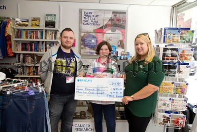 Grace Quinn from Lislea recenlty cut her hair in aid of The Little Priness Trust and raised a fantastic amount of £940 which she equally shared between Cancer Research Uk and Macmillan Cancer Support. Grace is pictured here presenting the cheques to Colin Coyle from The Cancer Research shop in Newry and Emma Ewings from Macmillan Cancer Support. R1730011
