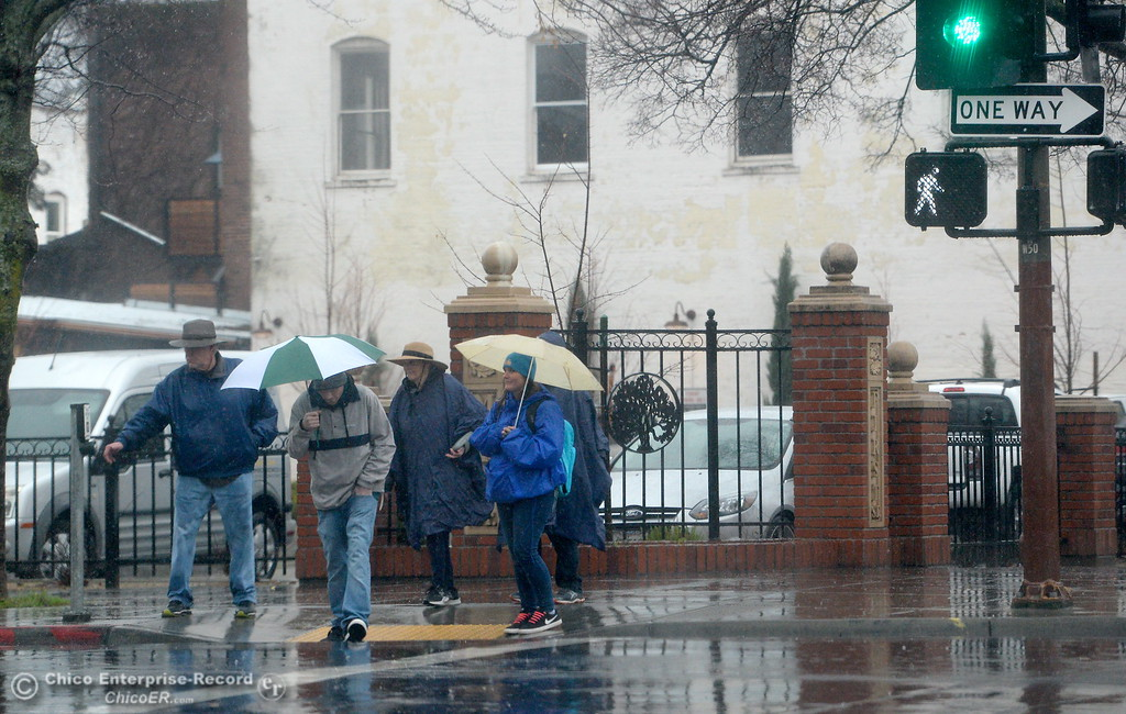 . A group of people wait to cross Main St. as rain falls in Chico, Calif. Mon. Jan. 8, 2018.  (Bill Husa -- Enterprise-Record)