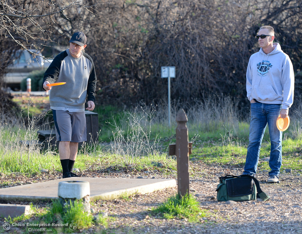 . Phil Mandelbaum watches as Bernie Bowman tees off at the Sherwood Forest disc golf course Friday January 12, 2018 in Chico, California. (Emily Bertolino -- Enterprise-Record)
