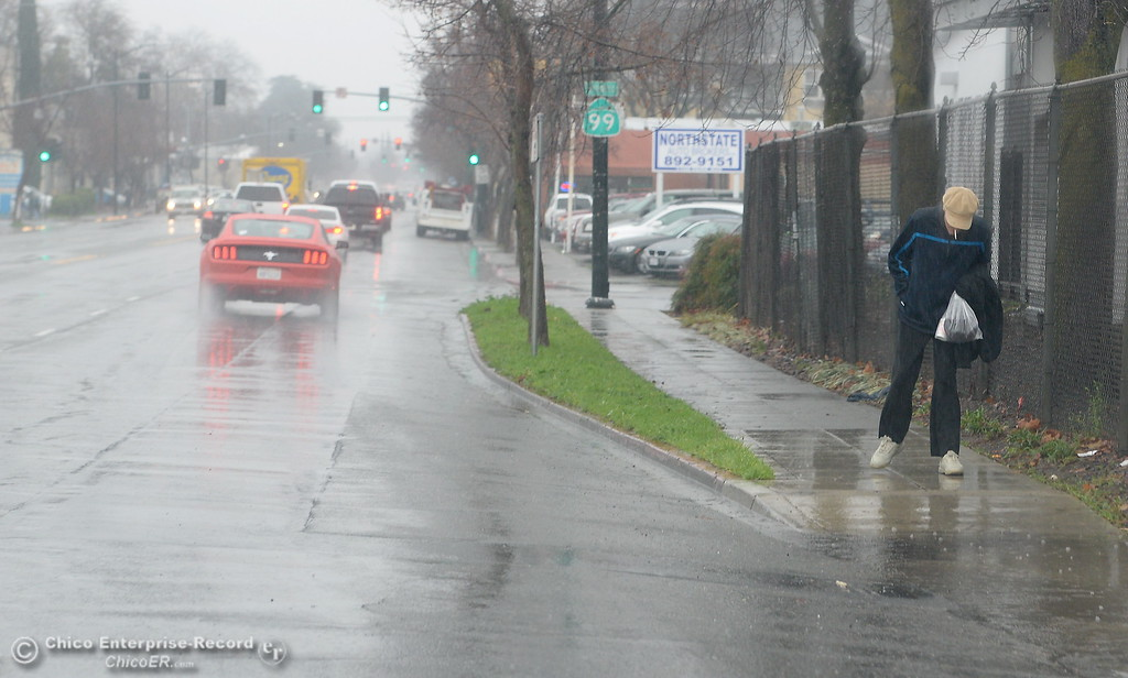. A man smokes a cigarette as he walks along Park Ave. while rain falls in Chico, Calif. Mon. Jan. 8, 2018.  (Bill Husa -- Enterprise-Record)