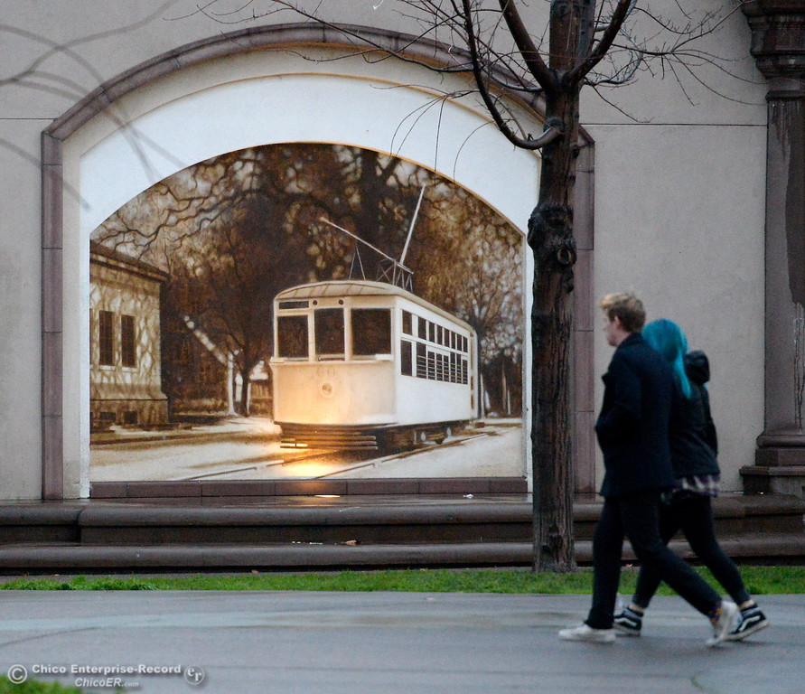 . A couple walk past the mural of a streetcar in City Plaza as a storm rolls over the area in Chico, Calif. Wed. Jan. 24, 2018.  Bill Husa -- Enterprise-Record)