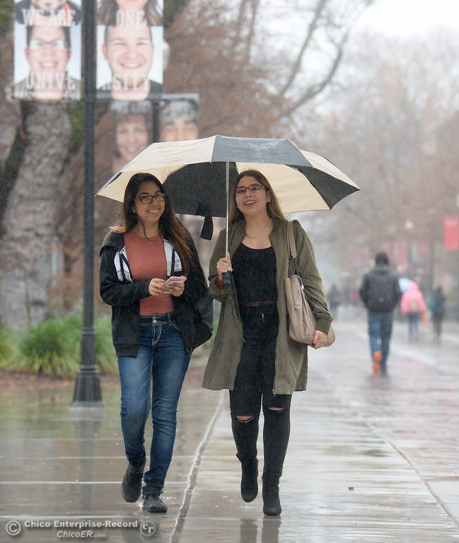 . Karina Velazquez left and Maria Zarco share an umbrella as students roam around campus as the spring semester begins on the CSUC campus Monday Jan. 22, 2018. (Bill Husa -- Enterprise-Record)
