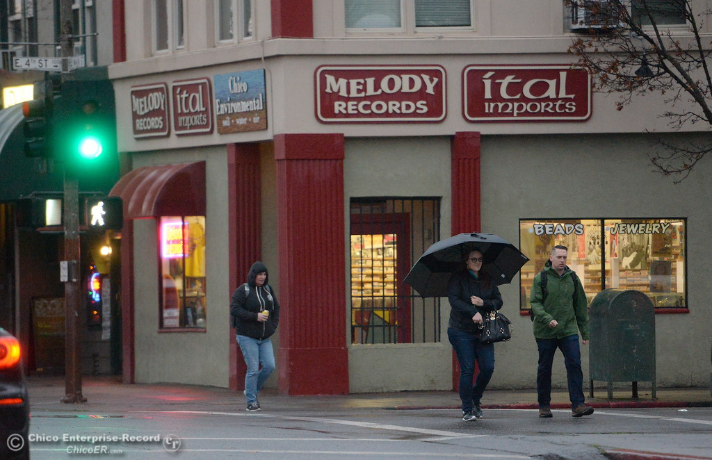 . People walk along Main Street near Melody Records as a storm rolls over the area in Chico, Calif. Wed. Jan. 24, 2018.  Bill Husa -- Enterprise-Record)