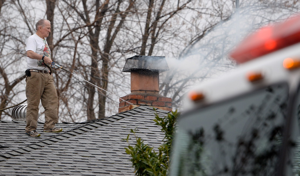 . 75-year-old James B. Husband waters down his chimney after his flue caught fire at 89 Oak Drive in Chico, Calif. Wed. Dec. 3, 2018. A firefighter said damage was minimal and there were no injuries. He also said that in a situation such as this, it is best to throw a cup of water inside of the stove and shut down the damper. (Bill Husa -- Enterprise-Record)