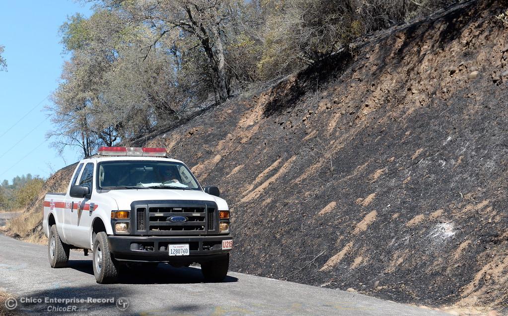 . A CAL FIRE truck patrols along Honey Run Road within the fire lines of the Honey Run Fire Thursday in Butte Creek Canyon.(Bill Husa -- Enterprise-Record)
