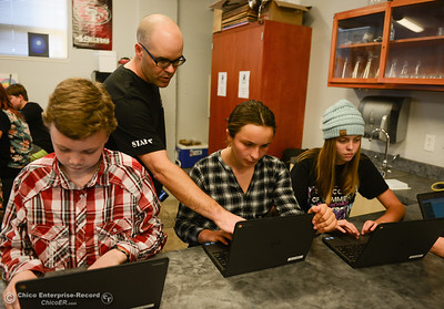 Left to right, Marcus Funk, 12, science teacher Darren Massa, Hayley Christopher, 12, and Harper Maiorano, 12, navigate a Chromebook laptops app to interact with the class, the teacher and parents Wednesday, Oct. 26, 2016, at Chico Country Day School in Chico, California. (Dan Reidel -- Enterprise-Record)
