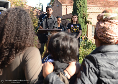 Students hold each other as Cross Cultural Leadership Center paraprofessional Kimani Davis, rear left, speaks while joined by event organizers Alexandra Wynter, rear center and Gillian Sammis, rear right, on stage during a solidarity rally on the Chico State University Glenn Hall lawn Wednesday, Nov. 16, 2016, in Chico, California. (Dan Reidel -- Enterprise-Record)