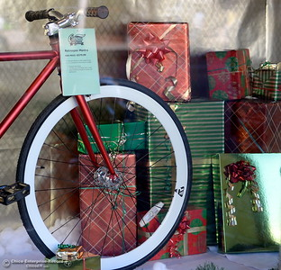 Christmas boxes and bows surround a bicycle in the window at Campus Bicycles in downtown Chico Monday. Chico was named one of the best towns for holiday shopping. Storefronts like this are already underway for the holiday shopping season Monday Nov. 14, 2016. (Bill Husa -- Enterprise-Record)