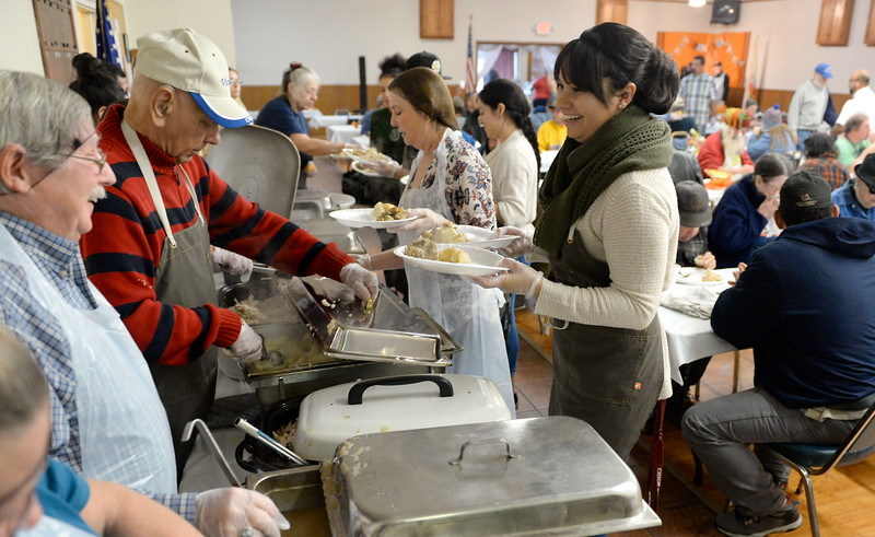 At right, Katalina Santamaria helps serve guests during the Salvation Army's annual thanksgiving dinner held at the Eagles Hall in Chico, Calif. Thurs. Nov. 23, 2017. (Bill Husa -- Enterprise-Record)