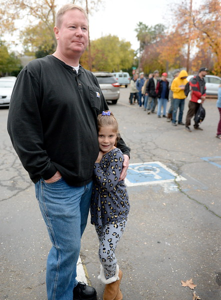 Kelly Chambers of Paradise and his daughter, a cancer survivor Maleree Chambers 7, ask where they can drop off clothes for the needy during the Salvation Army's annual thanksgiving dinner held at the Eagles Hall in Chico, Calif. Thurs. Nov. 23, 2017. (Bill Husa -- Enterprise-Record)