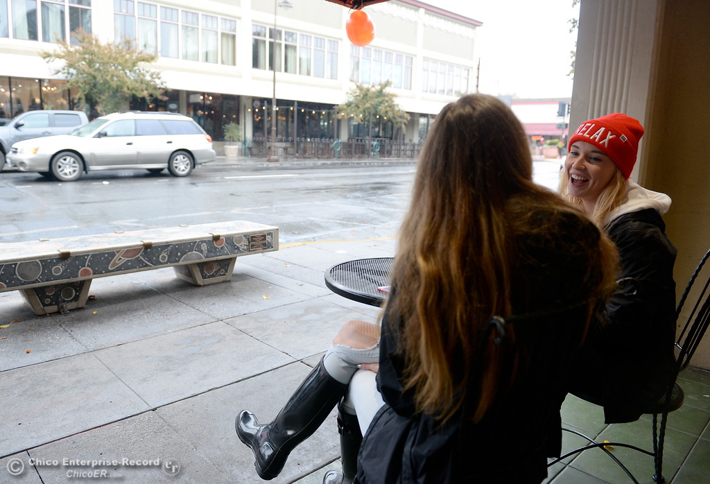 ". Tiana Echols left and Alex Grandy enjoy a little candy as they enjoy the rainy weather along Third St. in downtown Chico, Calif. Fri. Nov. 3, 2017. ""We wanted to people watch and enjoy the weather\"" said Echols. (Bill Husa -- Enterprise-Record)"