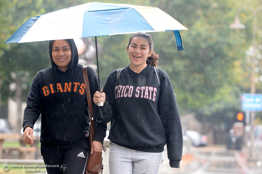 . CSUC students Nataly Palafox, left and Shooshanig Berumen share an umbrella as they walk near City Plaza in downtown while rain falls in Chico, Calif. Fri. Nov. 3, 2017. (Bill Husa -- Enterprise-Record)