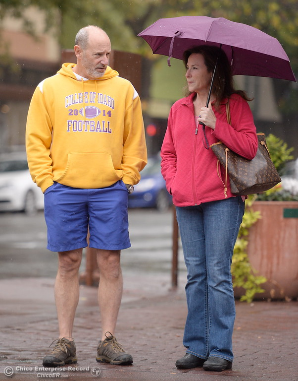 . Brian Cothern, a CSUC Alumnis from 1983 and Leslie Vollenweider choose different attire for their walk in downtown as rain falls in Chico, Calif. Fri. Nov. 3, 2017. (Bill Husa -- Enterprise-Record)