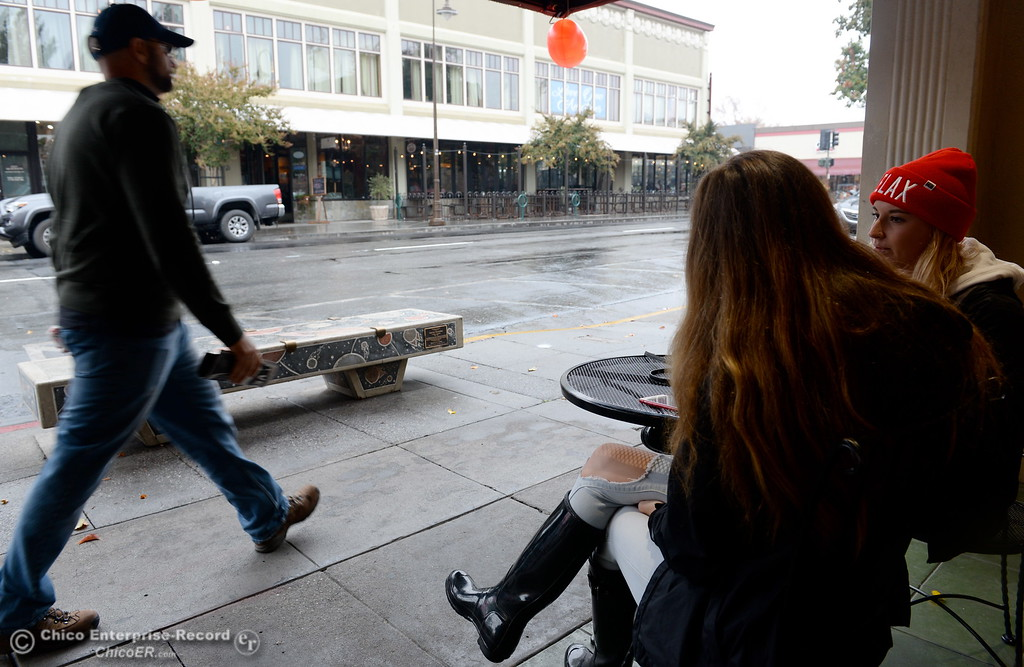 ". Tiana Echols center and Alex Grandy enjoy a little candy as they enjoy the rainy weather along Third St. in downtown Chico, Calif. Fri. Nov. 3, 2017. ""We wanted to people watch and enjoy the weather\"" said Echols. (Bill Husa -- Enterprise-Record)"