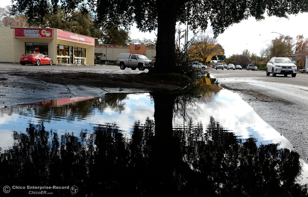 . Vehicles drive past a large puddle that seems to appear after each storm near a donut shop along The Esplanade in Chico, Calif. Monday Nov. 27, 2017. (Bill Husa -- Enterprise-Record)